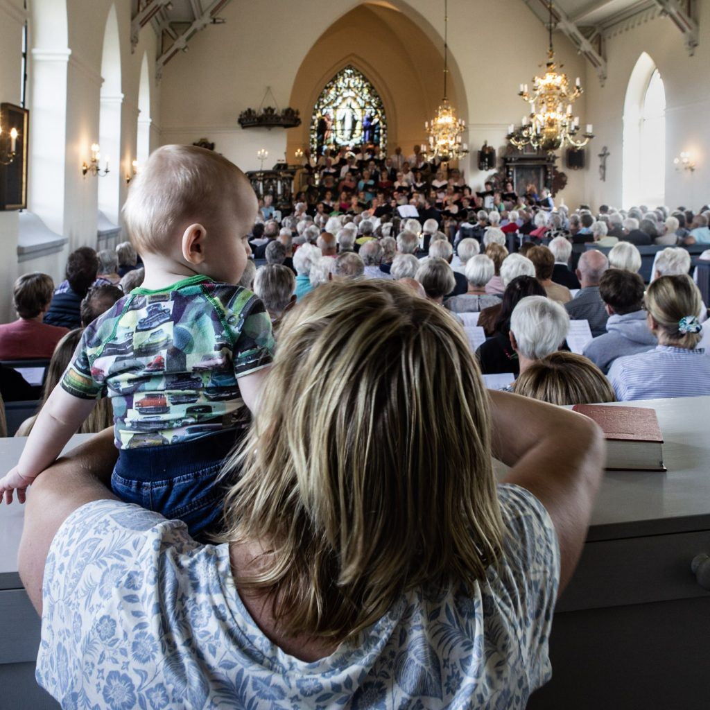 En litet barn tittar ut över överfull kyrka